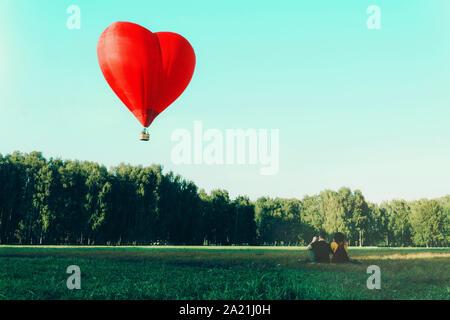 Junge Frau und ein Mann sitzen auf Gras und Suchen am Roten Heißluftballon in Form von Herzen. Liebe und Zukunft gemeinsam Konzept.
