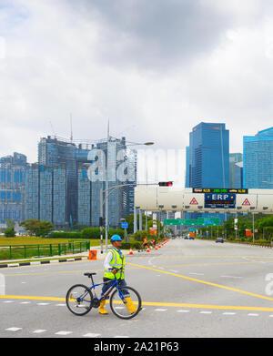Singapur - FEBTUARY 16, 2017: Baustelle Arbeiter in Helm und Weste Kreuzung Straße mit Fahrrad, Singapore Downtown Skyline im Hintergrund - Stockfoto