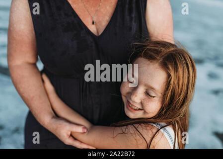 Seitenansicht der glückliche junge Tochter umarmen Mutter im Ozean bei Dämmerung