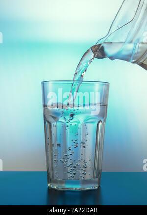 Wasser mit Luftblasen im Glas. Gießen Sie Wasser aus einem Krug in ein Glas. Licht durch ein Glas. Kreative Zusammenfassung Hintergrund. - Stockfoto