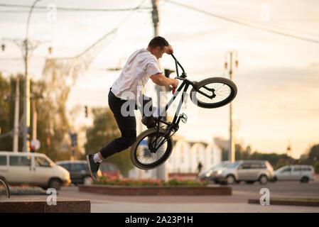 Der Kerl auf dem BMX, ein Trick, springt von der Brüstung. - Stockfoto