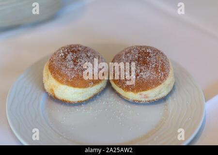 Essen, Zwei Berliner (Krapfen) liegen auf einem weißen Teller. Mit Berliner oder Krapfen genannt ist ein siedegebäck aus Hefeteig oder brandmasse. - Stockfoto
