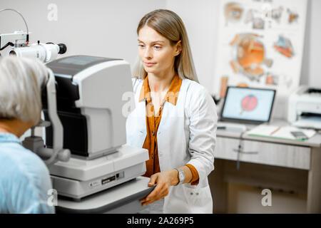 Augenarzt die Augen eines älteren Patienten mit digitalen Mikroskop während einer medizinischen Untersuchung in der ophthalmologischen Büro - Stockfoto
