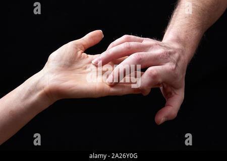 Männliche und weibliche Hände zusammen mit Emotionen auf schwarzem Hintergrund - Stockfoto