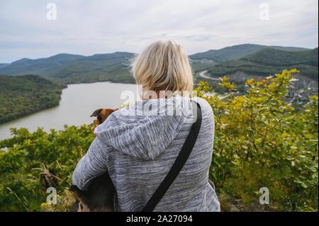 Hundehalter und Ihr Haustier suchen im Abstand oben auf dem Hügel. Ansicht von hinten. - Stockfoto