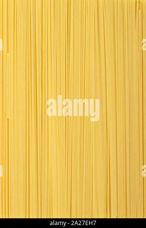 Dünne Nudeln in Reihen angeordnet. Gelb italienische Pasta. Lange Spaghetti. Rohe spaghetti Tapete. Essen Hintergrund Konzept. - Stockfoto