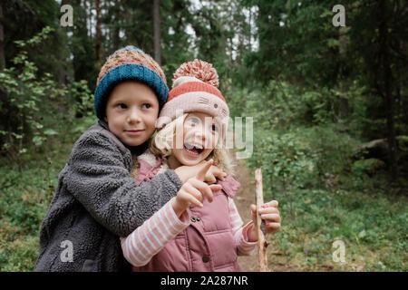 Bruder seine Schwester lachen, während man durch den Wald umarmen Stockfoto