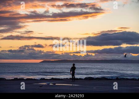 Port Talbot, Großbritannien. 01 Okt, 2019. Ein Surfer an der Aberavon Beach in Port Tallbot beobachtet, wie die Sonne über dem Wasser an der Swansea geht heute Abend duting einen Bruch in der nassen und windigen Wetter. Credit: Phil Rees/Alamy leben Nachrichten