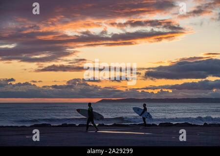Port Talbot, Großbritannien. 01 Okt, 2019. Surfer an Aberavon Beach in Port Tallbot zusehen, wie die Sonne untergeht, über das Wasser an der Swansea heute Abend duting einen Bruch in der nassen und windigen Wetter. Credit: Phil Rees/Alamy leben Nachrichten
