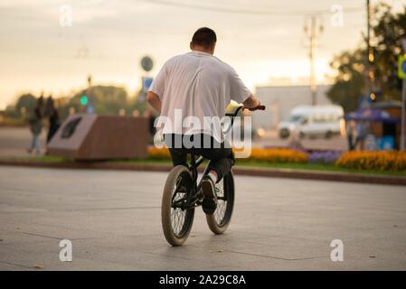 Der Kerl fährt auf dem BMX, auf dem Sitz sitzt. - Stockfoto