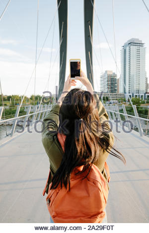Junge Frau mit Rucksack mit Fotohandy auf städtischen Brücke - Stockfoto