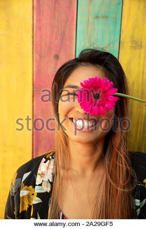 Portrait fröhlicher, verspielter junge Frau mit leuchtenden rosa Gerber Daisy - Stockfoto