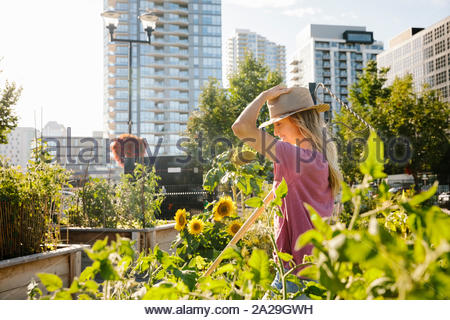 Glückliche junge Frau mit Sonnenhut in sonniger, städtischen Gemeinschaft garten - Stockfoto