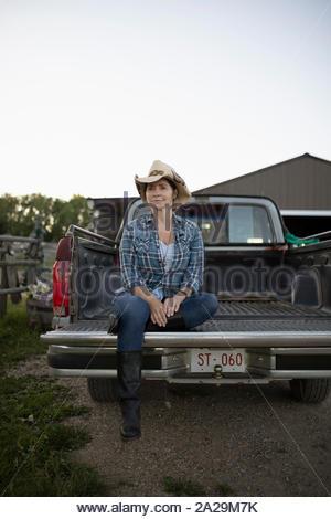 Reife Frau in Cowboyhut sitzen auf der Rückseite des Pickup Truck - Stockfoto