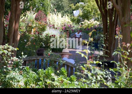 Rückseitige Ansicht des alten Paar sitzt auf der Bank im Garten spülen - Stockfoto