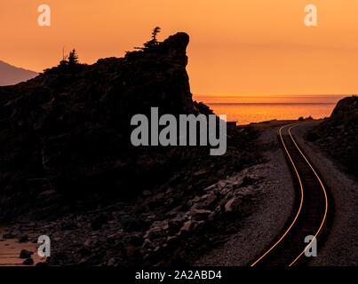 Bahngleise an einer schönen felsigen Küste mit Sonnenuntergang und Stahlbahnen, die orange und gelb leuchten. Turnagin Arm, Seward Highway, Alaska. - Stockfoto
