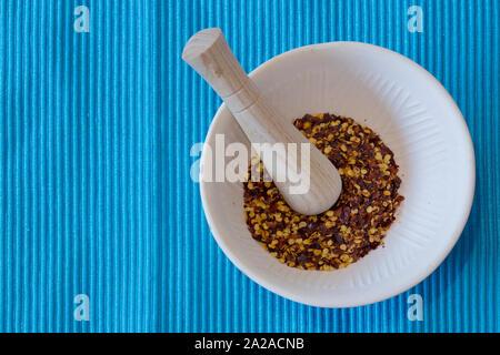 Chiliflocken in einem Stößel und Mörser auf einem blau gestreiften Unterlage. - Stockfoto