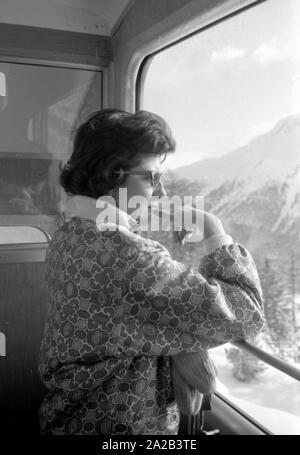 Am Tag der Hochzeit des iranischen Schahs mit Farah Diba, Reporter besucht seine vor kurzem geschiedene Ehefrau, Soraya, die in St. Moritz war an diesem Tag. Das Bild zeigt sie in einer Gondel auf dem Weg zu einer Piste, von mehreren Journalisten und Fotografen begleitet. - Stockfoto