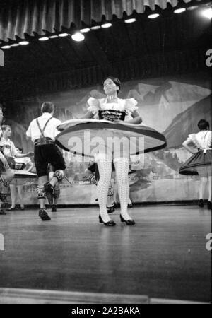 Eine Tänzerin in Tracht mit Flying Rock während einer Aufführung von traditionellen bayerischen Volkstänze in einem Kurort in Bayern. - Stockfoto