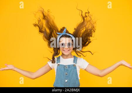 Das gute Gefühl fabelhafte Haar. Adorable Mädchen mit lockigem Haar winken auf gelben Hintergrund. Wenig Haar Modell mit Mode schauen. Kleines süßes Mädchen mit langen brünetten Haaren. Friseur und Schönheitssalon. - Stockfoto