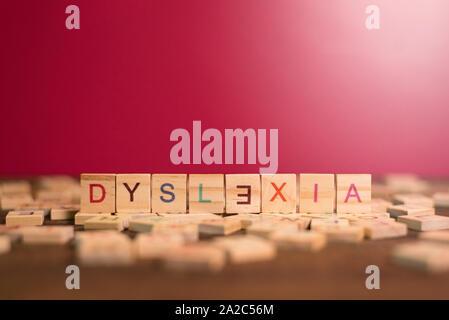 Holz- alphabet Blöcke mit Legasthenie Wort in der Mitte auf holztisch vor rosa Hintergrund. Konzept der Legasthenie Bewusstsein und menschliche Gehirn entwickeln. - Stockfoto