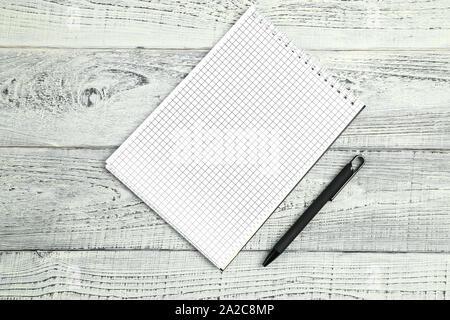 Notizbuch aus Papier mit Kugelschreiber auf Holz isoliert Hintergrund - Stockfoto