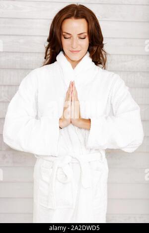 Schöne junge Frau in einem weißen Bademantel mit ihre Hände im Gebet - Stockfoto