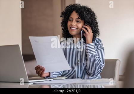 Lächelnd weibliche Unternehmer sprechen über ihr Handy und Lesen von Dokumenten - Stockfoto