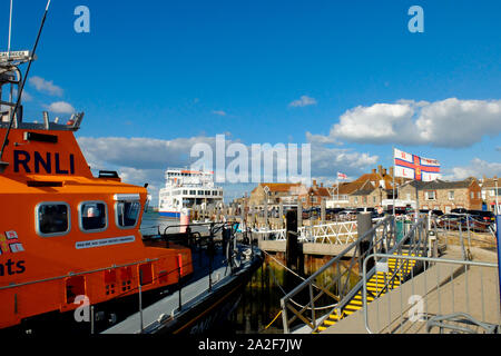 Yarmouth Hafen auf der Isle of Wight mit wightlink Fähren und die rnli Flagge über dem Rettungsboot station - Stockfoto