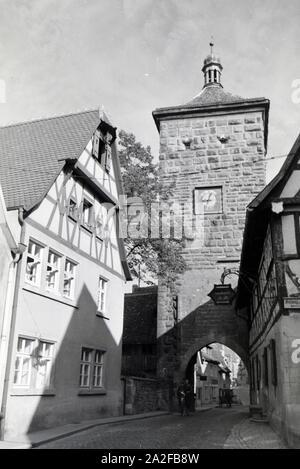 Ein Fahrradfahrer fährt durch das Sieberstor in Rothenburg o.d. Tauber, Deutschland 1930er Jahre. Ein Radfahrer fährt durch die siebers Gate/Sieberstor in Rothenburg o.d. Tauber, Deutschland 1930. - Stockfoto