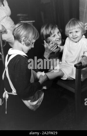 Zwei der Vierlinge von Brücken kümmern sich um Ihr jüngstes Geschwisterkind, Deutsches Reich 30er Jahre. Zwei der vierlinge von Brücken auf der Suche nach ihrer jüngsten Geschwister, Deutschland 1930. - Stockfoto