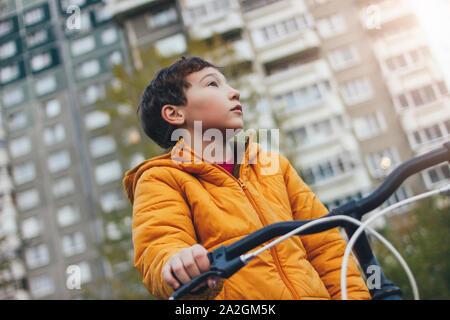 Cute tween Junge in der gelben Jacke auf dem Fahrrad in der Stadt Straße, Herbst - Stockfoto