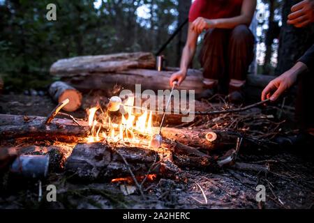 Es sind zwei Personen frittieren marshmeloo auf dem Scheiterhaufen auf einer Wanderung, an einem warmen Sommerabend. - Stockfoto