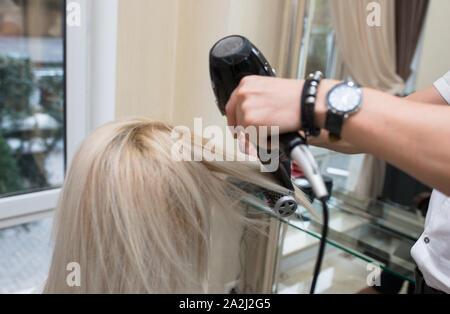Junge Schönheit blond attraktive Frau an Friseur. In der Nähe von Grau Silber Platin Kamm, Fön, Konzept Cut Friseursalon, weibliche Stilist. Master Vorbereitung - Stockfoto