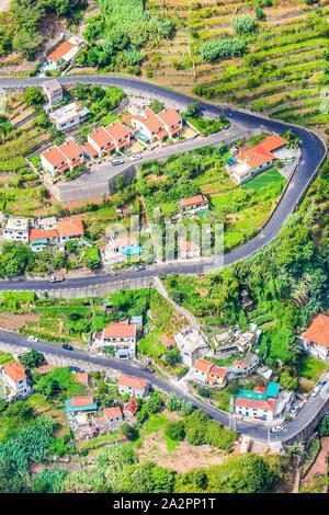 Luftaufnahme von einem Dorf Curral das Freiras, Madeira, Portugal. Land Häuser, grüne Terrassenfelder und malerischen Serpentinenstraße von oben fotografiert. Antenne Landschaft. Reisen vor Ort.