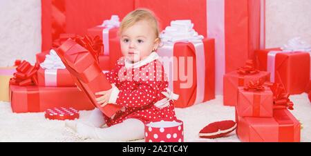 Little Baby spielen in der Nähe von Pile der roten Geschenkboxen verpackt. Geschenke für Kinder Weihnachten. Mein erstes Weihnachten. Die Freude des babys erstes Weihnachten mit der Familie. Baby erstes Weihnachten einmal im Leben. - Stockfoto
