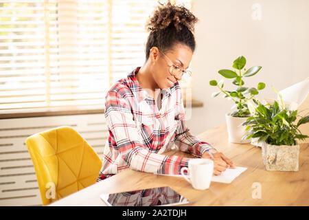 Portrait von schönen jungen afrikanischen amerikanischen lächelnde Frau, arbeiten auf dem Desktop, während Sie im Büro sitzen. - Stockfoto