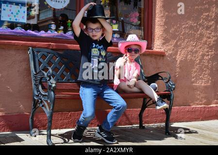 Ein Junge seine schwarze Cowboyhut und kleine Mädchen in rosa Cowboyhut und rosa Sonnenbrille Einstellung blinkt ein Friedensabkommen unterzeichnen, sitzen auf einer Bank vor einem Store - Stockfoto