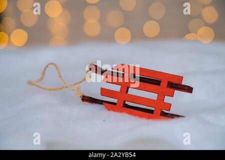 Weihnachten Komposition mit Rot Holz Weihnachtsmann Schlitten, Tannenzapfen und Xmas Tree Kugeln über verschwommenen hellen Hintergrund. Weihnachtskarte. Weihnachten und N - Stockfoto