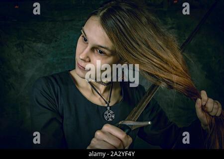 Porträt der jungen langhaarigen Frau in ein mittelalterliches Kostüm. Ständige pose mit einem Schwert an ihren Haaren an dunklen Studio Hintergrund - Stockfoto