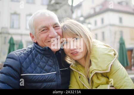 Gut aussehender älterer Mann begrüßt seine junge blonde Frau Ausgabe Zeit zusammen im Freien in der antiken Stadt im frühen Frühjahr oder Herbst.