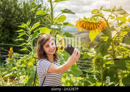 Eine hübsche junge Tausendjährigen brünette Frau, eine selfies neben einem sonnenblumenfeld. - Stockfoto