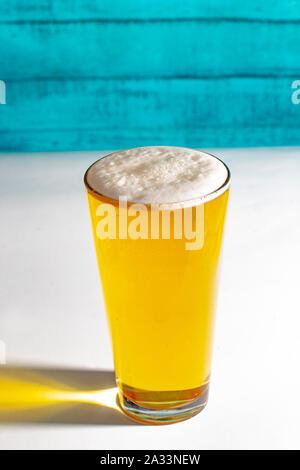 Licht Pint Bier auf einem weißen Tisch mit grünem Holz- wand.