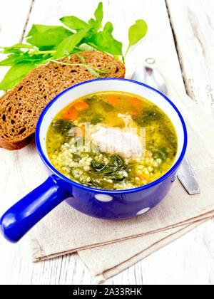 Schweinerippchen Suppe mit Couscous und Spinat in eine blaue Schale auf dem Handtuch, Brot auf Holzbrett Hintergrund - Stockfoto
