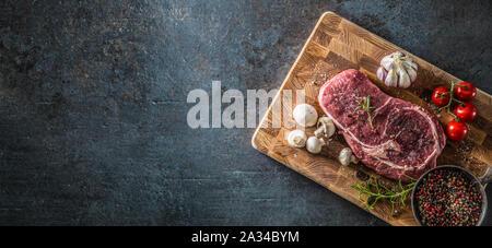 Rib Eye Steak Salz Pfeffer Gewürze, Knoblauch und Pilzen. Rohes Rindfleisch Fleisch auf butcher Board - oben auf Ansicht - Stockfoto