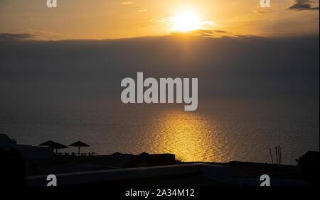 Die Sonne hinter Wolken am Horizont auf die Ägäis von einer Klippe Restaurant in Oia gesehen - Stockfoto