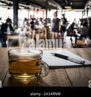 Heißen Tee mit Notizbuch und Stift auf Holztisch im Coffee Shop unter Licht