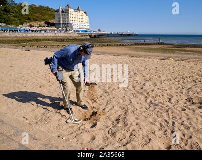 Mann im Herbst Outfit zu Fuß den Strand mit einem Metalldetektor durch Sand sieben auf der Suche nach Kostbarkeiten auf der Küstenstadt auf Llandudo, Wales. - Stockfoto