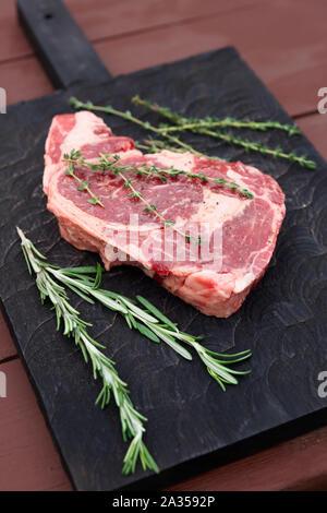 Raw Rib-eye-Steak auf dem Schwarzen Brett - Stockfoto