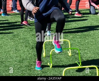 Ein High School Leichtathletik Team macht Geschwindigkeit Arbeiten an laufenden Form über einen Fuß gelb mini Hürden auf grünem Rasen. - Stockfoto